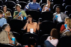 Woman Talking on Cell Phone During Movie --- Image by © image100/Corbis