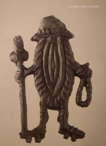 Badge of a vulva with legs dressed as a medieval pilgrim with hat, rosary and walking stick.
