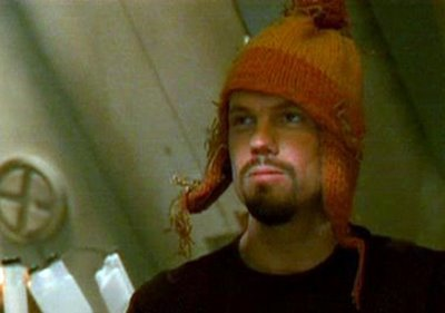 Adam Baldwin as Jayne Cobb in sci-fi series Firefly wearing a distinctive orange and yellow bobble hat with earflaps.