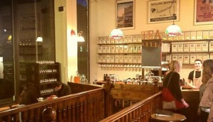 Inside a warm and inviting tea house with a wall full of tea canisters.