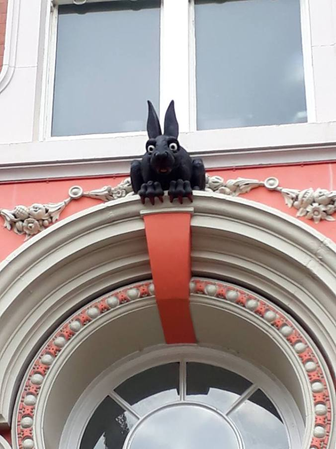 A black rabbit sculpture sits above an ornate white and pink door frame. He has blood-red nails and teeth!
