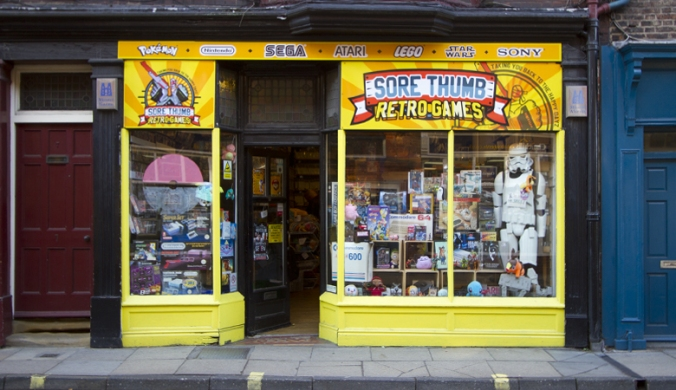 Frontage of Sore THumbs Retro Games, the window is jam packed with games and a life size Stormtrooper.