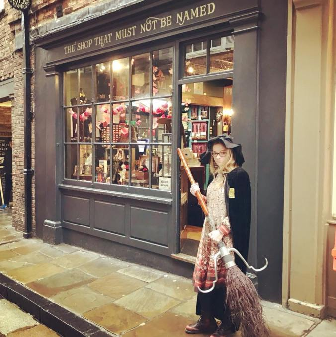 A witch with broom stands in front of an aged looking shop front, The Shop That Must Not Be Named.